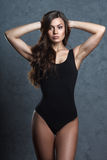 Woman in black leotard posing on grey background Royalty Free Stock Photo