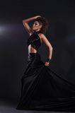 Woman in black long dress over dark background Stock Images