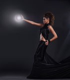 Woman in black long dress over dark background royalty free stock images