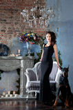 Woman in black long dress sitting on chair with dog (doberman) Stock Photography