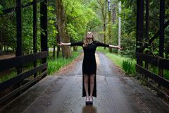 Woman in Black Long Sleeve Dress Standing on Black Bridge in the Forest Leaning Sky during Daytime Stock Images
