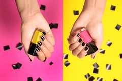 Woman with black manicure holding nail polish bottles on color background. Top view royalty free stock photography
