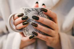 Woman With Black Manicure Holding White and Grey Floral Ceramic Cup Royalty Free Stock Image