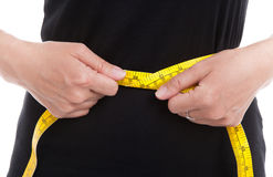 The woman in black measures her waist circumference with measuri. Ng tape on white background stock photos