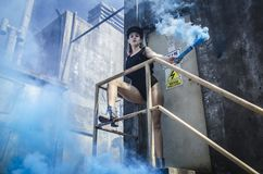 Woman in Black Onepiece Holding Smoke Bomb Near Close Door stock photos