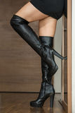 Woman in black over knee boots. Close up shot of female legs in over knee boots leaning at a mirror in an apartement Stock Photo