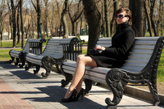 Woman in black overcoat sitting on bench Stock Image