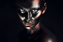 Woman in black paint in dark Stock Photo
