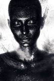 Woman in black paint in dust. In studio Stock Images