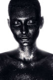 Woman in black paint in white light Royalty Free Stock Photos