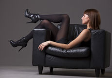 Woman in black pantyhose and heels. Young woman in black pantyhose and heels relaxing on the chair royalty free stock photos