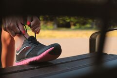 Woman in Black and Pink Sneaker Tying Lace of Her Shoe Stock Photography