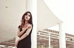 Woman in Black Plunging Neck Dress Standing Behind White Concrete Pillar Royalty Free Stock Photo