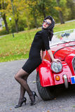 Woman in black posing on retro car front Stock Photo