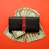 Woman black purse wallet with dollar banknotes on the red background royalty free stock images