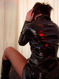 Woman in black pvc coat and red fishnet stockings. Young woman dressed as a dominatrix is turned away from the viewer, wearing shiny black pleather coat Stock Images