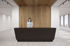 Woman at black reception counter. Portrait of a businesswoman standing with crossed arms at a black reception counter in an office lobby. 3d rendering Stock Photography