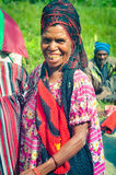 Woman with black and red headcloth. Sara village, Papua New Guinea - July 2015: Native woman with black and red headcloth dressed in colourful shirt smiles to Stock Photos