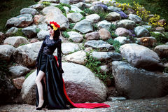 Woman in black and red lace dress and flowers on stone outdoor background full size Royalty Free Stock Images