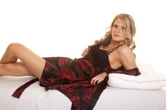 Woman black and red nightgown lay on back looking Royalty Free Stock Photo