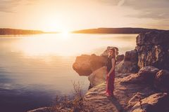 Woman in Black and Red Sleeveless Dress Standing Near Large Body of Water during Sunset Stock Image