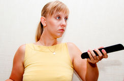Woman with black remote. Blonde woman with black remote control in hand Stock Photo