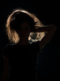 Woman in black shadow with messed up hair. Front view of woman in black shadow with messed up hair, on black background Stock Image