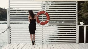 Woman in Black Sheath Dress Beside Swim Ring on Dock Royalty Free Stock Image