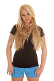 Woman black shirt blue shorts thumbs in pocket Royalty Free Stock Photography