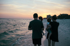 Woman in Black Shirt Carrying His Son in the Seashore during Sunset Stock Images