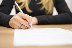 Woman with black shirt is signing legal document Royalty Free Stock Photography
