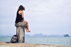 Woman in Black Shirt Sitting Near Body of Water during Daytime Stock Photo