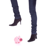 Woman in black shoes breaking a piggy bank Royalty Free Stock Photo