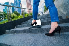 woman black shoes with a heel steps attack the notebook stock images