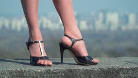 Woman in black shoes on heels at blurred city background. Beautiful legs of businesswoman. The woman in black shoes on heels is standing at the blurred city stock video footage