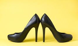 Woman black shows on yellow. Background Stock Images