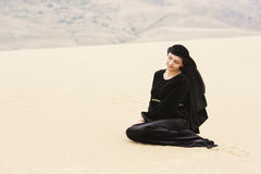 Woman in black sitting on sand Royalty Free Stock Images