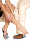 Woman black skirt rub leg one shoe off Stock Image
