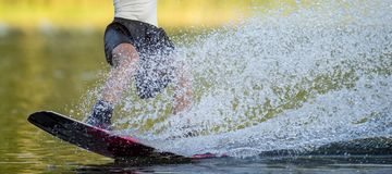 Woman in a black skirt on a water ski is engaged in extreme spor. Ts. Wakeboard sport and girl Royalty Free Stock Photo