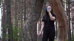 Woman in black sports attire in the woods or Park, drinking water from a bottle after a run. Female quenches her thirst on a Sunny day with water stock video