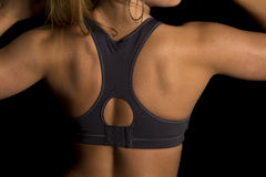 Woman in black sports bra back close arms up. A close up of a woman in her black sports bra flexing Stock Photos