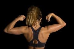 Woman in black sports bra back flexing Stock Image
