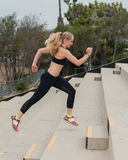 Woman in black sports bra climbing stadiums. Athlete in black tights training on concrete steps stock image