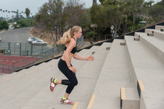 Woman in black sports bra climbing stairs. Athlete in black tights training on concrete steps stock photo