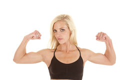 Woman black sports bra flex biceps. A woman flexing her arms showing off her nice biceps stock image