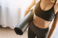 Woman in Black Sports Bra With Grey Leggings Carrying Yoga Mat Royalty Free Stock Photo