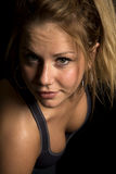 Woman in black sports bra very close looking. A woman in her black sports bra, sweating after a work out Royalty Free Stock Images