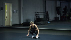Woman in black sportswear doing burpees exercise in a gym stock video footage