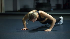 Woman in black sportswear doing burpees exercise in a gym stock footage