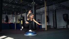 Woman in black sportswear doing lunges on the Bosu and the TRX in gym stock footage